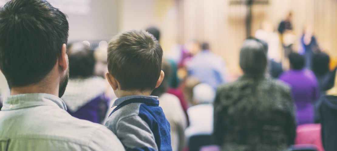 Father with his son participate at christian congregation worship